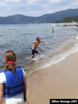 James leaves the water after completing a 12-hour swim across the entire length of Lake Tahoe. (AP Photo/Jillian Savage)