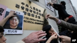 香港民主抗議者舉著銅鑼灣書店老板桂民海的肖像(2016年1月19日)。