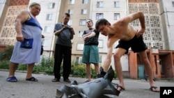 ພົນລະເມືອງໃນທ້ອງຖິ່ນ ນຳສິ້ນສ່ວນຂອງລູກປືນໃຫຍ່ ມາໃຫ້ເບິ່ງ ຫຼັງຈາກ ທີ່ມີການໂຈມຕີດ້ວຍປືນໃຫຍ່ ຂ້າມຄືນຢູ່ເມືອງ Donetsk ໃນພາກຕາເວັນອອກຂອງ Ukraine ມື້ວັນສຸກ ທີ 8 ສິງຫາ 2014.