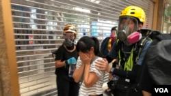 有市民不知道警方在德福花园商场施放催泪弹驱散示威者,被催泪烟波及,双眼刺痛,由示威者护送到安全地点 (摄影:美国之音汤惠芸)