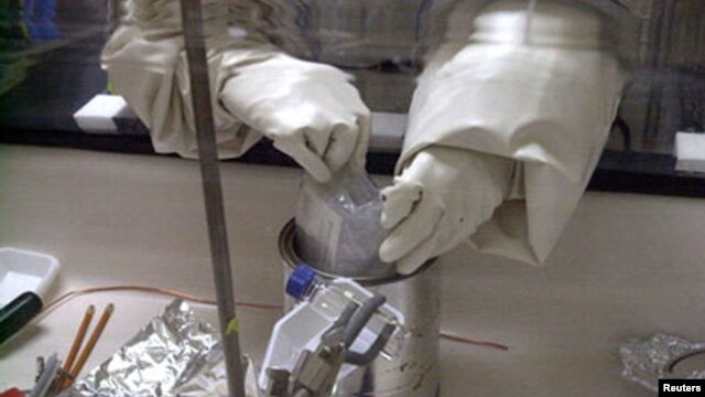 FILE - A scientist examines a package for anthrax spores.