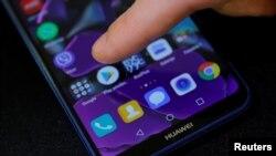 一名男子的手指正要點擊華為手機上的谷歌應用程序商店。(2019年5月20日)