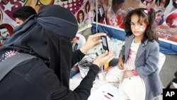 Nadia Abudllah photographing a young girl during the uprising in Sana'a, Yemen, February 20, 2012.