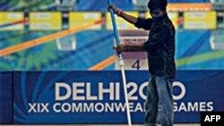 Một công nhân Ấn đang tẩy rửa hồ bơi trong khu thi đấu