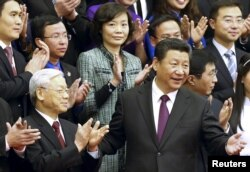 FILE - China's President Xi Jinping, front right, gestures to Vietnam's Communist Party General Secretary Nguyen Phu Trong as they pose for a group photo with Chinese and Vietnamese youths at the Great Hall of the People in Beijing, April 7, 2015.