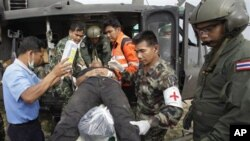 An injured Thai soldier on a stretcher is helped to board a helicopter to be transferred to a hospital following the clashes between Thailand and Cambodia in Surin province, northeastern Thailand, April 28, 2011.