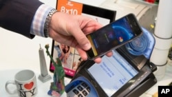 FILE - A customer makes a purchase with a MasterCard using Apple Pay on the iPhone 6 at Walgreens in New York's Times Square, Oct. 20, 2014.