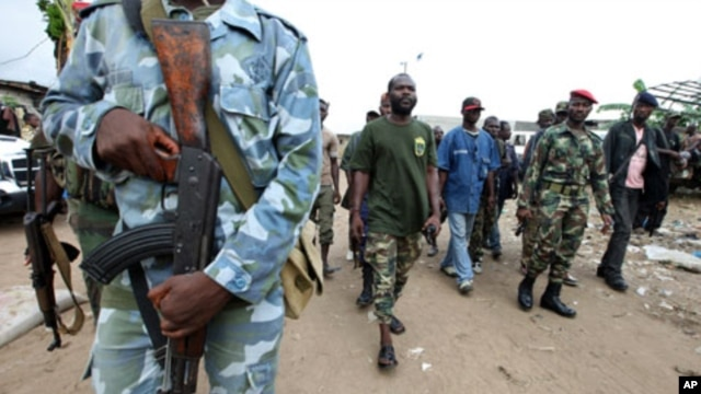 "A man known as Commander Bauer, the chief of a group of fighters which calls itself the ""invisible commandos"", walks with his men in northern Abidjan's Abobo district. Fighting in Ivory Coast's main city is spreading and the death toll from a power strugg"