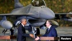 El presidente Barack Obama estrecha la mano a su homólogo polaco, Bronislaw Komorowski, con el fondo de un avión caza F-16.