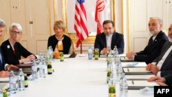 U.S. Secretary of State John Kerry, left, awaits the start of a meeting with Iranian Foreign Minister Mohammad Javad Zarif, second from right, after his return from Iran for international negotiations on nuclear policy in Vienna, Austria, June 30, 2015.