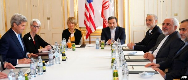 FILE - U.S. Secretary of State John Kerry, left, awaits the start of a meeting with Iranian Foreign Minister Mohammad Javad Zarif, second from right, after his return from Iran for international negotiations on nuclear policy in Vienna, Austria, June 30, 2015.