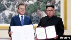 South Korean President Moon Jae-in and North Korean leader Kim Jong Un pose for photographs with the joint statement in Pyongyang, North Korea, September 19, 2018. Pyeongyang Press Corps/Pool via REUTERS TPX IMAGE.