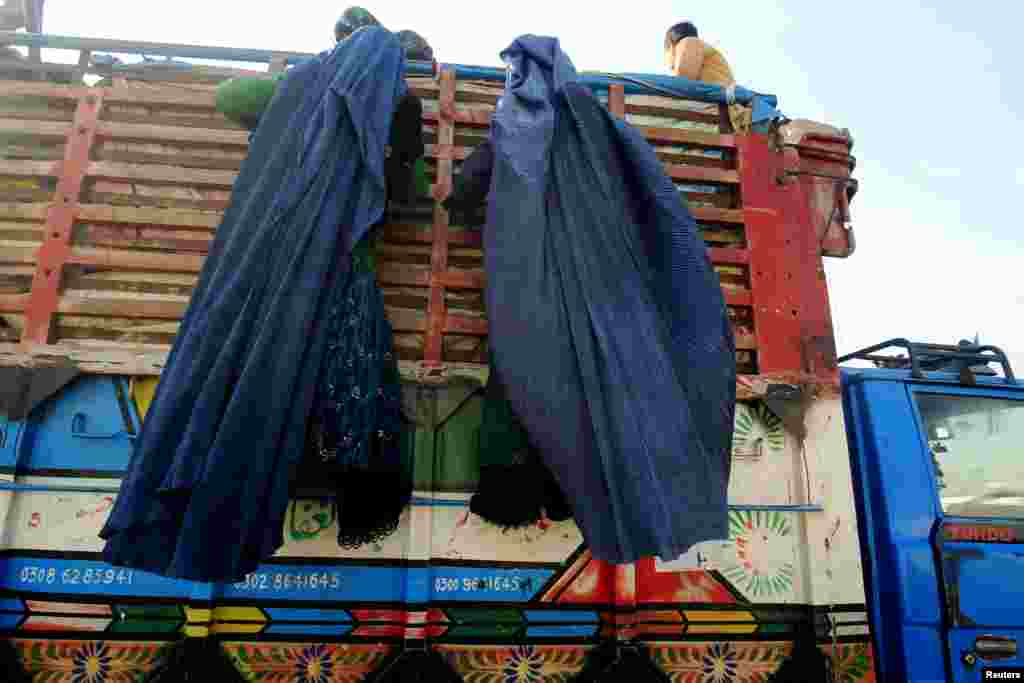 Afghan refugee women, clad in a burqa, climb on a truck to be repatriated to Afghanistan, at the United Nations High Commissioner for Refugees (UNHCR) office on the outskirts of Peshawar, Pakistan.