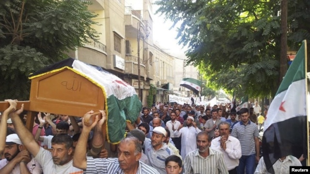 Residents carry the coffin of Muhammad Mousa, whom protesters say was killed by forces loyal to Syria's President Bashar al-Assad, during his funeral in Yabroud near Damascus July 21, 2012.