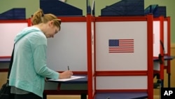 FILE - A woman casts marks her ballot during primary voting in Durham, N.C., May 8, 2018.