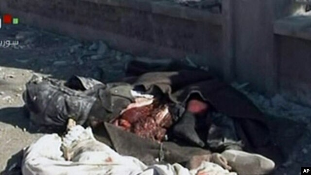 An image grab taken off the official Syrian TV shows the bodies of the victims covered with blankets at the scene of a blast in Syria's second largest city of Aleppo, February 10, 2012.