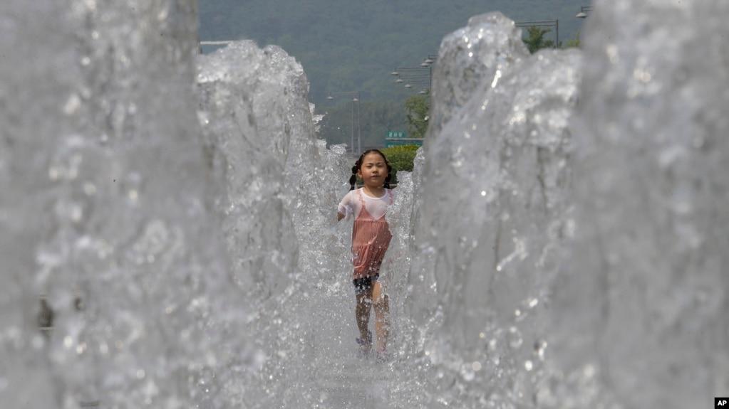 Một cô bé chạy qua một vòi nước công cộng tại Seoul để bớt nóng ngày 16/6/2017.