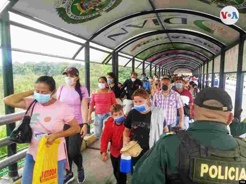 Migrantes con tapabocas cruzando la frontera colombo-venezolana.