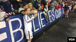 French player takes a selfie with fans at RFK Stadium in Washington after France defeated the USA, 3-0, to win the SheBelieves Cup.