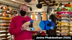 Co-owner of Uncle Funkys Boards, Jeff Gaites, holds a Surfskate inside his shop in Manhattan, New York March 25, 2021.