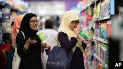 FILE - Malaysian women chat as they shop at a mall in Petaling Jaya outside Kuala Lumpur, Malaysia, Oct. 30, 2014.
