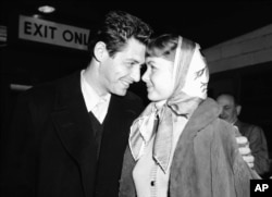 FILE - Singer Eddie Fisher and his fiancee, actress Debbie Reynolds, have eyes only for each other at Idlewild Airport, April 19, 1955, in New York on arriving by plane from England.