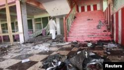 Seorang pria Afghanistan memeriksa lokasi ledakan bom yang terjadi saat pesta pernikahan di privinsi Samangan, Sabtu (14/7).