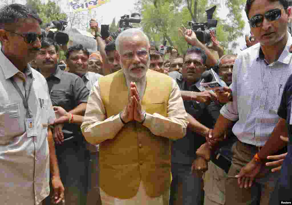 Hindu nationalist Narendra Modi (center), the presumptive prime minister of India, gestures as he arrives to seek blessings from his mother, Heeraben, at her residence in Gandhinagar, May 16, 2014.