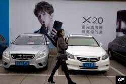 A woman walks past an advertisement featuring teen idol Lu Han, also known as China's Justin Bieber in Beijing, China, Oct. 21, 2017. China works to stifle celebrities as it seeks to dictate the values the nation's youth should embrace. It's part of the m