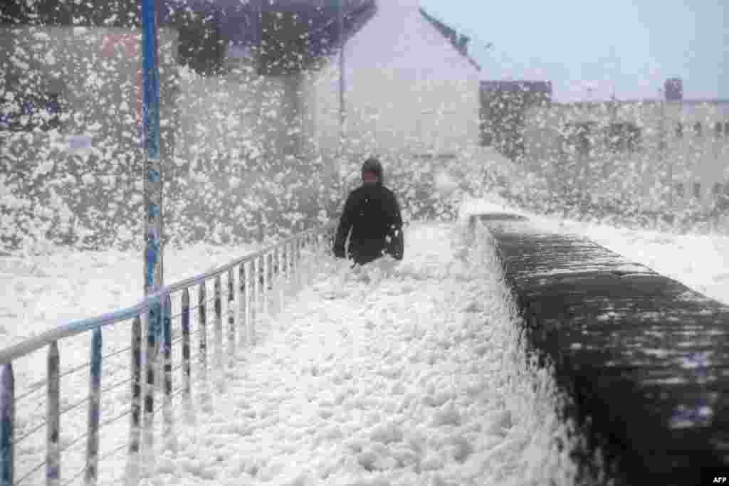 A person walks as sea foam washes up on the frontwalk in Saint-Guenole, western France, as storm Dennis sweeps accross Brittany.
