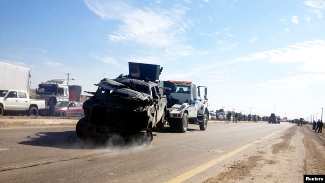 A police vehicle is towed after a suicide bomb attack in Taji, 20 km (12 miles) north of Baghdad, February 5, 2013.