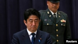 Japan's PM Shinzo Abe attends a flag return ceremony to mark the return of the Japan Self-Defense Force troops stationed with the UN Disengagement Observer Force in Golan Heights, at the Defense Ministry in Tokyo, January 20, 2013.