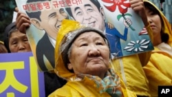 "Former comfort woman Kil Un-ock who was forced to serve for the Japanese troops as a sexual slave during World War II, attends a rally against a visit by Japanese Prime Minster Shinzo Abe to the United States, in front of the Japanese Embassy in Seoul, South Korea, Wednesday, April 29, 2015. Abe has sidestepped a question on whether he would apologize for the sexual enslavement of women by Japan's army during World War II. The letters at a card read "" Oppose the alliance between U.S. and Japan."" (AP Photo/Ahn Young-joon)"