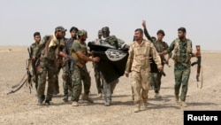 FILE - G-7 leaders are expected to discuss efforts to defeat the Islamic State. Here, Iraq's Shi'ite paramilitaries and Iraqi security forces hold an Islamist State flag pulled down in Anbar province, May 26, 2015.