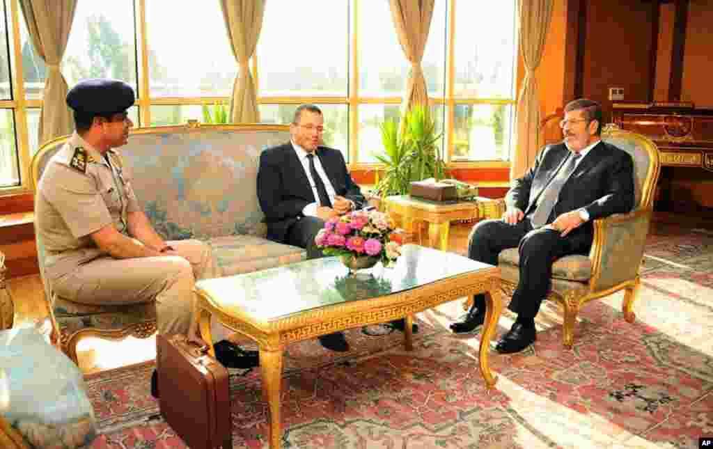 埃及總統府7月1日公佈的照片顯示埃及總統穆爾西(右)在開羅與總理坎迪勒和國防部長塞西中將(左)交談。
