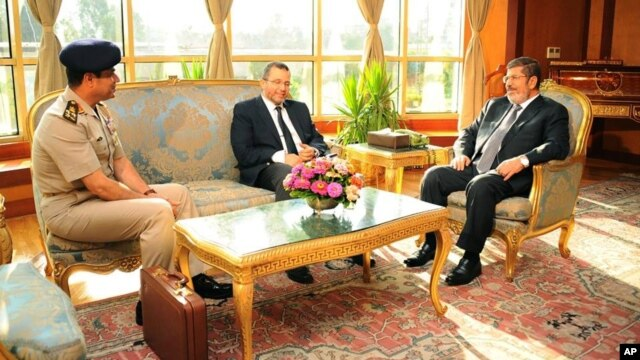 In this photo released by the Egyptian Presidency, July 1, 2013, Egyptian President Mohammed Morsi, right, meets with Prime Minister Hesham Kandil, center, and Egyptian Minister of Defense, Lt. Gen. Abdel-Fattah el-Sissi, left in Cairo.