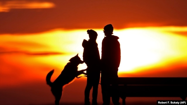 A couple pauses to take in the view of a colorful sunset while walking their dog in a park, Thursday, Jan. 28, 2016, in Portland, Maine.