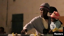 ຜູ້ຍິງຄົນນຶ່ງອູ້ມລູກໄປປ່ອນບັດຢູ່ສະຖານທີ່ປ່ອນບັດເລືອກຕັ້ງ ໃນເມືອງ Domboshava, ຫ່າງຈາກນະຄອນ Harare ປະມານ 45 km ໃນວັນທີ 31 ກໍລະກົດ 2013