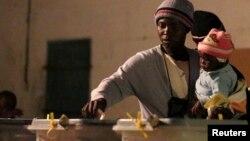 Uma mulher zimbabueana acompanhada de filho, exercendo o direito de voto nas eleições gerais da semana passada
