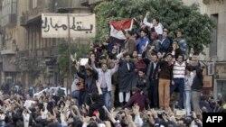 """Učesnici protesta u Kairu stoje na vojnom oklopnom vozilu pored znaka na kojem piše """"Dole Mubarak"""