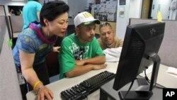 Career center specialist Sun Gaddis (L) helps job seeker Kaston Joshua (C), while Rudy Martin looks on at WorkSource Oregon, in Tualatin, Oregon, July 2012.