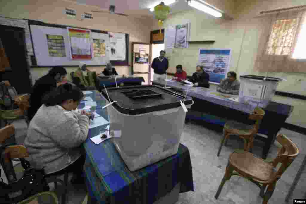 Election workers and ballot boxes are seen inside a polling station during a referendum on the new constitution in Cairo, Jan. 15, 2014.