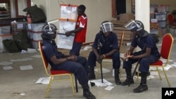 FILE - Zambian police sit at the Civic Center in Lusaka, Zambia, as election volunteers carry ballot boxes, September 22, 2011.