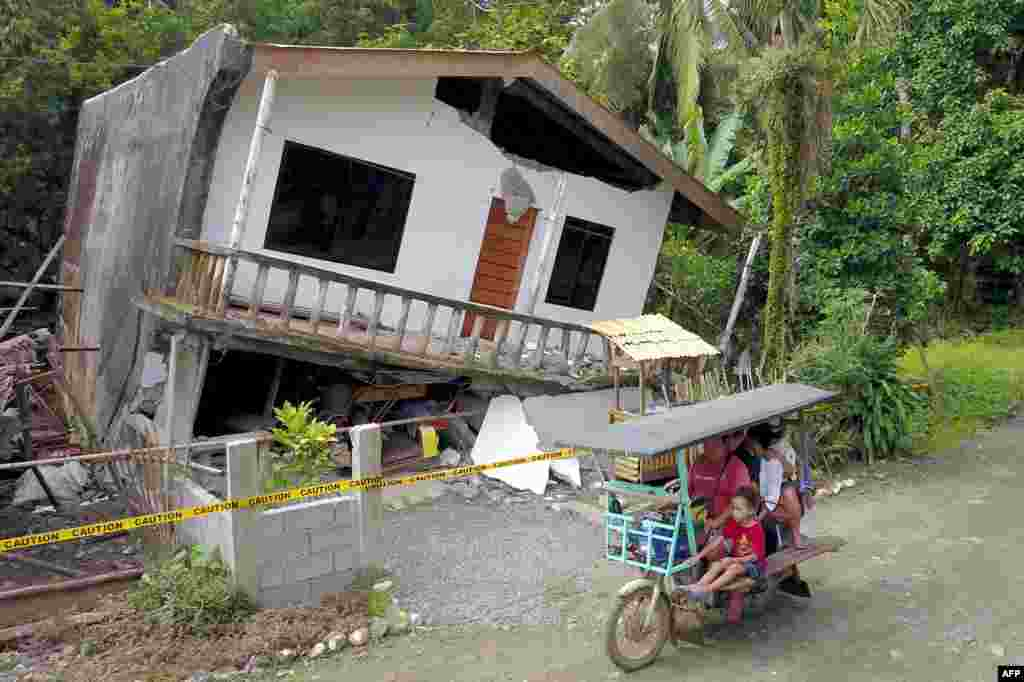 A motorist drives past a destroyed house after a large earthquake that hit Surigao City, in southern island of Mindanao, Philippines. Fifty-one people were injured and several homes, churches and other buildings damaged  when an earthquake sent terrified residents of the southern Philippines fleeing their homes before dawn, police said.