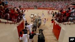 Corredores y toros llegan a la plaza de toros durante el octavo y último encierro de las fiestas de San Fermín en Pamplona, en el norte de España, el domingo 14 de julio de 2019.