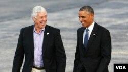 ປະທານາທິບໍດີ Barack Obama ແລະຜູ້ແທນສະພາຕຳ່ ພັກ ເດໂມແຄຣັດ ທ່ານ Mike Michaud ກຳລັງຢ່າງທີ່ເດີ່ນບິນ