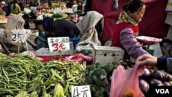 Para warga di Beijing berbelanja keperluan sehari-hari di sebuah pasar sayuran. Kenaikan harga-harga akan menjadi tantangan utama ekonomi Tiongkok tahun depan.