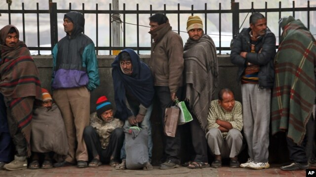 Impoverished and homeless people stand in a queue to receive free food from a volunteer organization in front of a temple, in New Delhi, India, January 1, 2013.