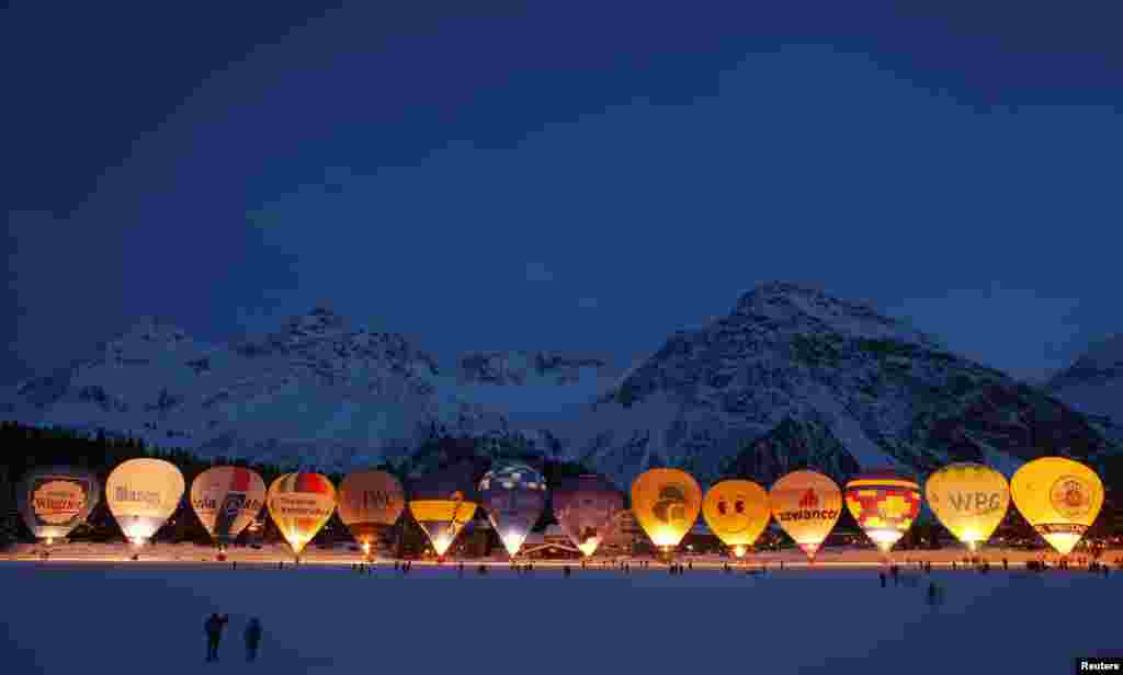 Spectators take pictures as hot air balloons are gathered on the frozen Upper Lake during International Balloon Week in the Swiss alpine resort of Arosa.