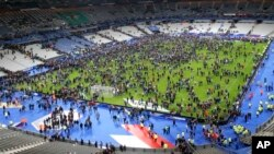 Para penonton memenuhi lapangan di stadion Stade de France tempat timnas Perancis bertanding melawan Jerman, setelah ledakan di luar stadion, Jumat malam (13/11).